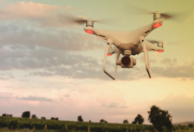 white drone hovering over field